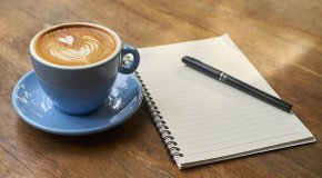 coffee, notebook, and pen on table
