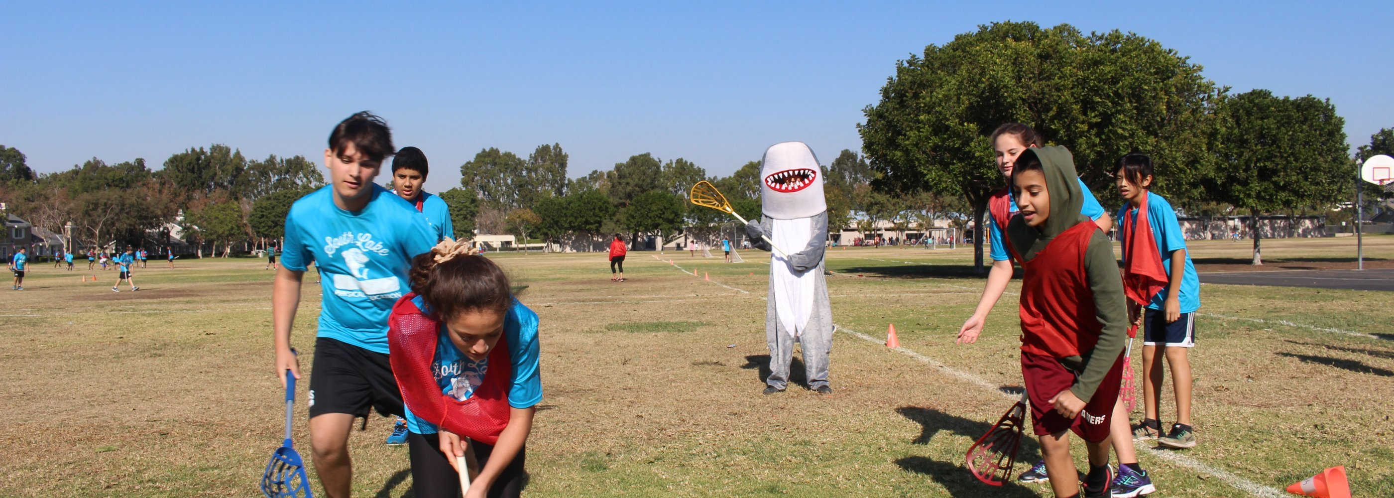 mascot playing on field with students